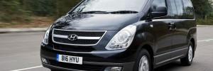 Hyundai H1 varebil, sort stor varebil som kjører lands landeveien.