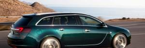 Opel Insignia Sports Tourer, mørke grønn metalic kjører på vei som slynger seg ved sjøen, pent vær og gode forhold.